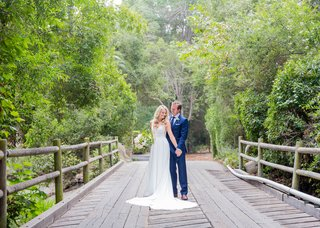 wedding-portrait-on-bridge-bride-in-sleeveless-wedding-dress-groom-in-blue-suit-bridge-santa-barbara