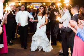 bride-and-groom-run-through-tunnel-of-guests-with-sparklers