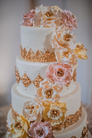 white-wedding-cake-with-golden-embellishments-yellow-pink-white-sugar-flowers