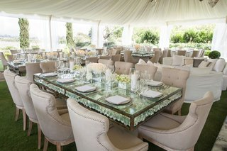 mirror-reception-table-with-upholstered-neutral-chairs-and-white-flowers-at-tent-wedding-reception