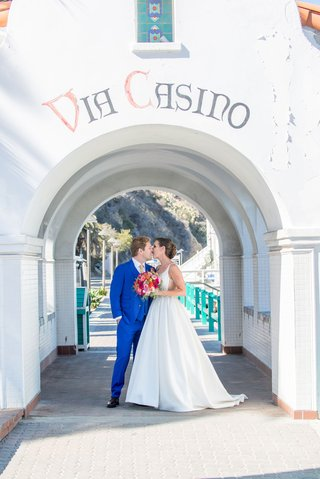bride-and-groom-kiss-under-arch-in-beach-wedding