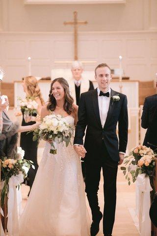 bride-in-strapless-reem-acra-wedding-dress-neutral-bouquet-groom-in-tuxedo-bow-tie-pastor-cross