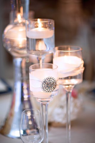 floating-candles-in-wedding-centerpiece-tall-glass-votives-with-ribbon-and-jewel-decal