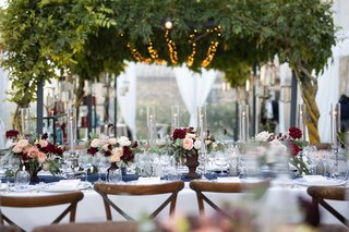 wedding-reception-under-canopy-of-greenery-with-twinkle-lights-vineyard-chairs-floral-centerpieces