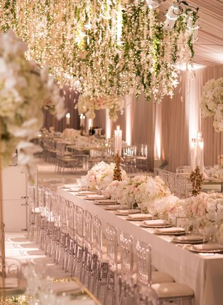 wedding-reception-blush-tent-long-table-clear-chairs-white-flowers-gold-candleholders-greenery-over