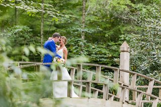 wedding-portrait-on-bridge-bride-in-hayley-paige-wedding-dress-groom-in-azure-blue-suit-woods