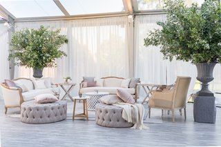 lounge-area-in-soft-neutral-colors-grey-quilted-ottoman-displays-of-greenery