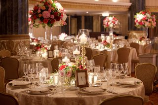 round-ballroom-wedding-reception-table-with-table-number-in-gold-frame-low-centerpiece-blush-marsala