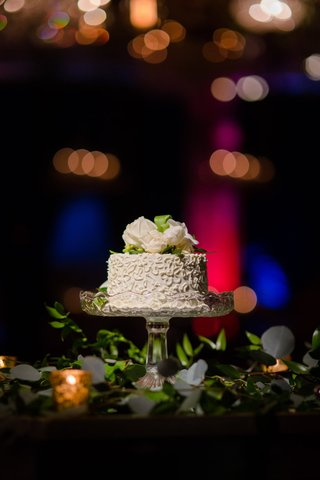 small-wedding-cake-on-glass-cake-stand-fresh-flowers-on-top-cutting-cake-only