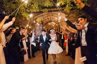 bride-in-second-wedding-dress-short-with-groom-going-through-guest-sparkler-tunnel-outdoors
