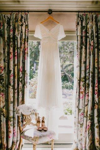 wedding-dress-hanging-up-in-window-with-sleeves-and-velvet-peep-toe-heels-pink