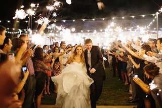 bride-in-a-strapless-martina-liana-dress-and-groom-in-black-suit-run-through-sparkler-send-off