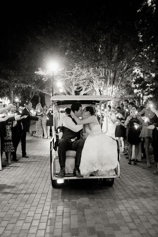 black-and-white-photo-of-bride-and-groom-on-back-of-golf-cart-after-wedding-sparkler-exit-guests