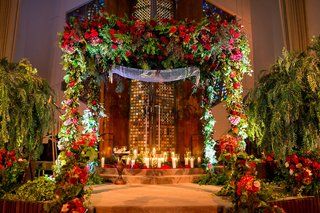 temple-jewish-wedding-with-lush-greenery-and-red-burgundy-flowers-at-chuppah-and-ceremony-stage