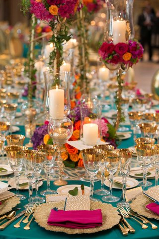turquoise-linens-gold-flatware-candles-in-glass-vases-pink-napkin-multi-colored-arrangements