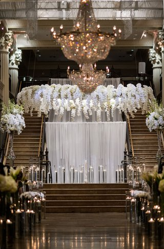 wedding-ceremony-stage-floating-candles-white-drapery-orchid-flowers-in-halo-wreath-over-vow-spot