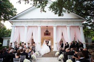 wedding-ceremony-on-porch-of-venue-outdoor-ceremony-lee-park-arlington-hall-pink-drapery