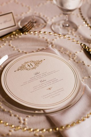 round-wedding-menu-with-double-lined-border-and-embellished-monogram-on-top-clear-charger-with-gold