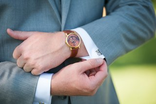 groom-in-grey-suit-watch-with-brown-leather-band-anchor-graphic-on-dial-silver-letter-k-cuff-link