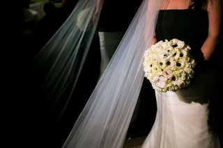 bride-in-a-gown-with-a-black-bodice-and-white-skirt-holding-a-bouquet-of-white-amaryllis