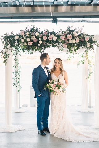 groom-in-cobalt-blue-suit-looking-at-bride-as-they-stand-under-chuppah-with-roses-in-shades-of-pink