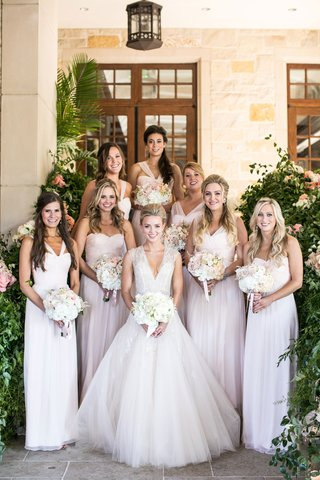 bride-and-her-bridesmaids-smile-and-hold-their-bouquets-blush-bridesmaid-dresses-mismatched-neckline