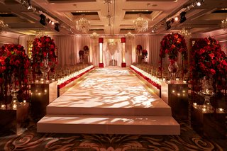 elevated-white-aisle-indoor-jewish-wedding-ceremony-red-roses
