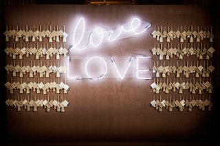 wedding-reception-escort-card-display-on-wall-with-love-neon-sign-white-light