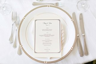 wedding-reception-place-setting-with-a-white-charger-with-gold-and-black-rim-and-menu