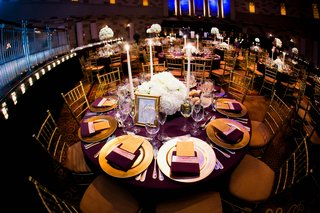 wedding-reception-table-at-gotham-hall-with-purple-tablecloth-and-gold-charger-and-white-centerpiece