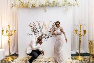 bride-in-second-wedding-dress-groom-in-white-tuxedo-sun-glasses-monogram-photo-booth-backdrop-gold