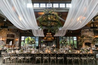 wedding-reception-long-table-iron-chandelier-greenery-white-drapery-vineyard-chairs-fireplace
