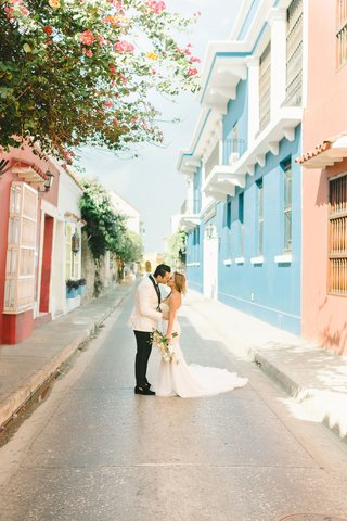 bride-and-groom-portrait-streets-of-colombia-colorful-houses-villas-apartments-shops-white-tuxedo