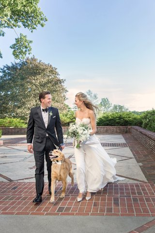 bride-in-flowing-wedding-dress-with-lace-bodice-and-groom-in-tuxedo-walking-dog