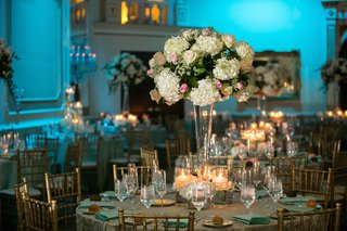 ballroom-with-blue-lighting-and-tall-flowers