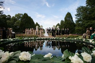 wedding-ceremony-in-front-of-pond-decorated-with-split-leaves-and-large-white-flowers