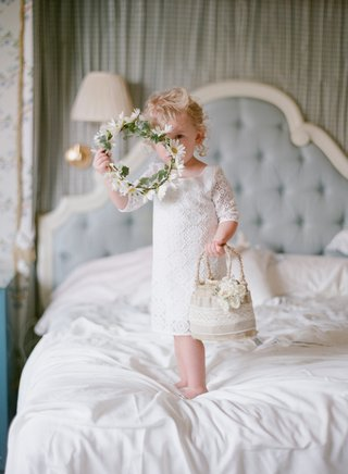 white-lace-three-quarter-sleeve-flower-girl-dress-on-bed