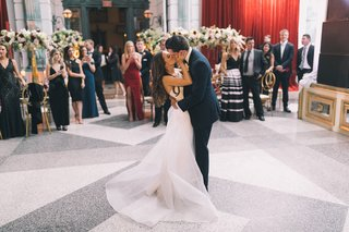 bride-in-romona-keveza-groom-in-tuxedo-kissing-on-middle-of-dance-floor