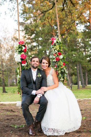bride-in-nardos-iman-wedding-dress-with-groom-on-rope-swing-decorated-with-flowers-and-garlands