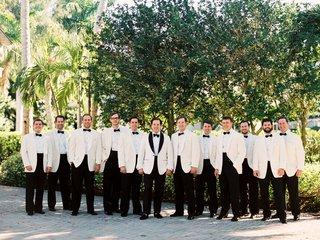 groom-in-white-tuxedo-jacket-black-lapels-and-groomsmen-in-ivory-jackets-black-bow-ties