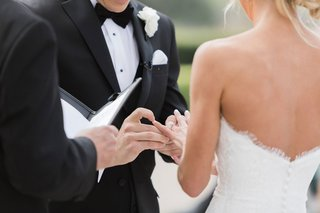 outdoor-wedding-ceremony-bride-in-strapless-wedding-dress-updo-groom-in-tuxedo-bow-tie-vow-exchange