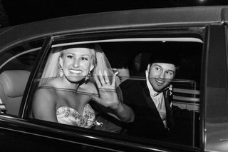 black-and-white-photo-of-couple-in-sedan-leaving-reception