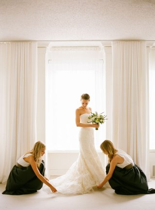 bridesmaids-in-black-skirts-and-white-tops-lay-out-brides-vera-wang-gown-train