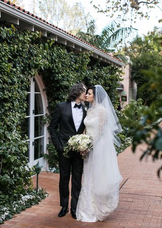 wedding-portrait-bride-in-veil-and-long-sleeve-wedding-dress-groom-tuxedo-bow-tie-kisses-cheek
