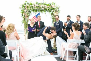 bride-in-allure-ball-gown-groom-in-navy-joseph-abboud-suit-dipped-for-first-kiss-as-husband-wife