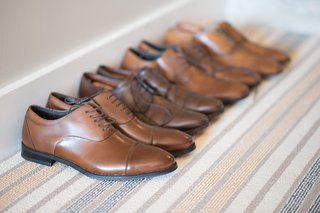 pairs-of-groomsmen-tan-leather-shoes-lined-up-against-the-wall