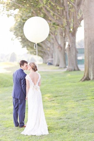 bride-in-a-lace-watters-dress-with-cap-sleeves-holds-white-balloon-kisses-groom-in-royal-blue-suit