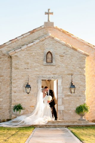 bride-and-groom-in-front-of-old-brick-church-in-texas