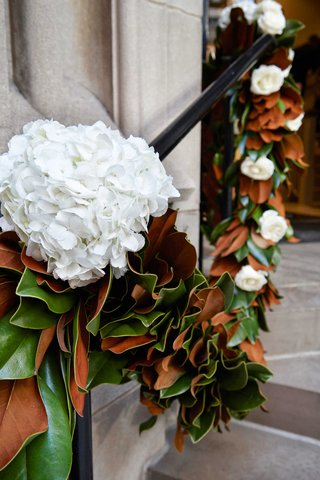 stairs-to-chicago-church-decorated-with-garland-of-magnolia-leaves-white-hydrangea-and-rose-flowers