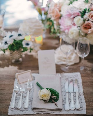 rustic-wood-reception-table-with-lace-place-mat-tan-napkin-and-white-rose-decoration